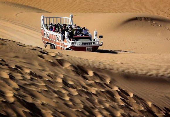Turistas passeiam pelo deserto num veículo especial